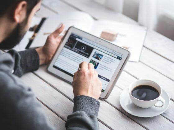 Mann schaut sich eine Webseite auf seinem Tablet an. Dabei stützt er sich auf einen weißen Holztisch und neben ihm steht ein schwarzer Kaffee in einer weißen Tasse.