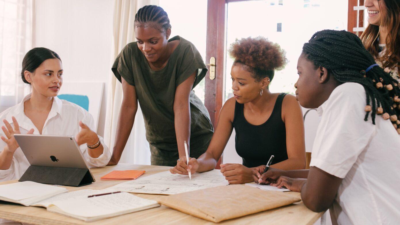 Fünf Frauen sitzen um einem Tisch mit Laptop und analysieren Veranstaltungsberichte